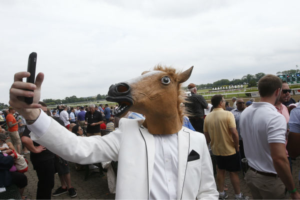 "<div class=""meta image-caption""><div class=""origin-logo origin-image none""><span>none</span></div><span class=""caption-text"">A spectator wearing a horse mask takes a selfie before the 147th running of the Belmont Stakes horse race at Belmont Park, Saturday, June 6, 2015, in Elmont, N.Y.  (AP Photo/ Jason DeCrow)</span></div>"
