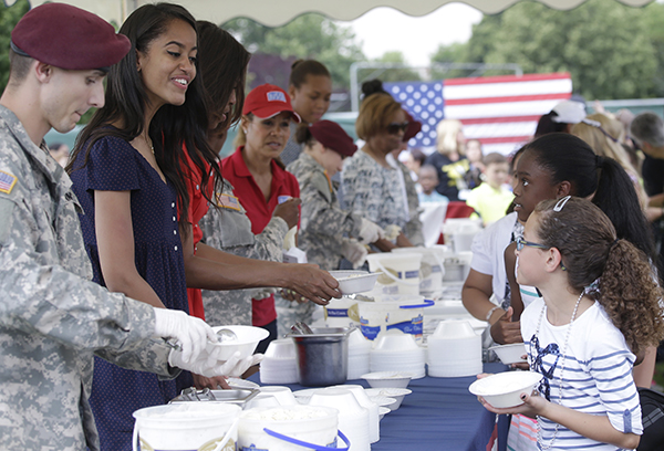 <div class='meta'><div class='origin-logo' data-origin='none'></div><span class='caption-text' data-credit='AP'>Michelle Obama and  Malia serve ice cream as she meets with soldiers and their families at the U.S. Army Garrison Vicenza, northern Italy, June 19, 2015. (AP Photo/Antonio Calanni)</span></div>