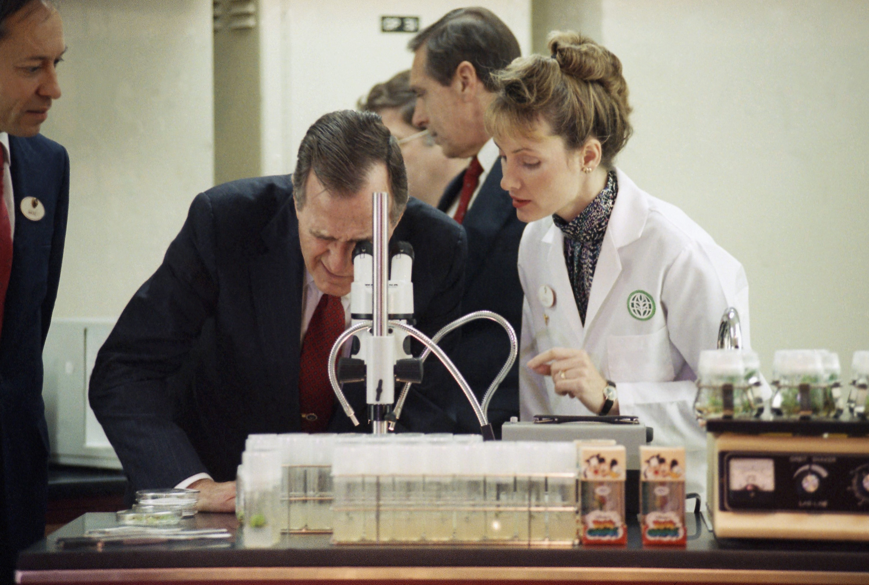 <div class='meta'><div class='origin-logo' data-origin='none'></div><span class='caption-text' data-credit='AP Photo/Barry Thumma'>President George H.W. Bush looks through a microscope as Dr. Lexie McKently, right, biotechnology research scientist at Disney World's Land Pavilion at Epcot Center.</span></div>
