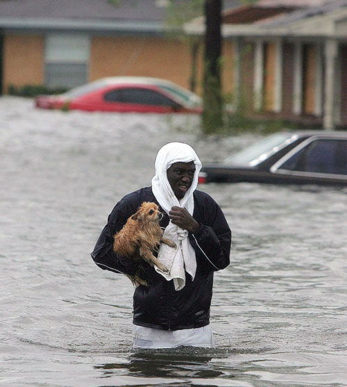 "<div class=""meta image-caption""><div class=""origin-logo origin-image none""><span>none</span></div><span class=""caption-text"">Jonathan Harvey wades through flood waters after rescuing his dog ""Cuddles"" from his flooded home after  urricane Katrina struck the Gulf Coast in Gulfport, Miss..   (Photo/JOHN BAZEMORE)</span></div>"