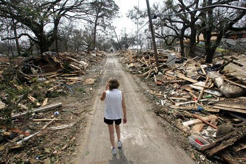 "<div class=""meta image-caption""><div class=""origin-logo origin-image none""><span>none</span></div><span class=""caption-text"">Rhonda Braden walks through the destruction in her childhood neighborhood, Wednesday  Aug. 31, 2005 in Long Beach, Miss.  (Photo/ROB CARR)</span></div>"