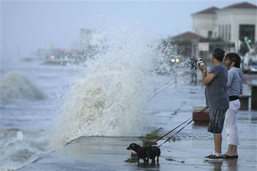 <div class='meta'><div class='origin-logo' data-origin='none'></div><span class='caption-text' data-credit='AP Photo/ Matt Slocum'>Debra Schmid, from right, her fiance Chuck Schmid, and their dogs Gertrude and Mildred watch as waves from approaching Hurricane Ike crash into the seawall, Sept. 12, 2008.</span></div>