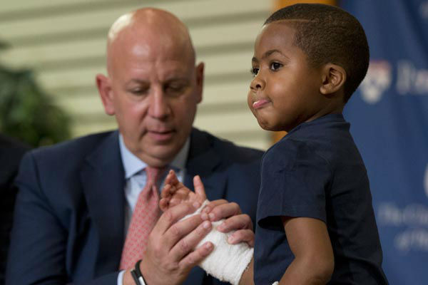 <div class='meta'><div class='origin-logo' data-origin='none'></div><span class='caption-text' data-credit='AP Photo/ Matt Rourke'>As Dr. L. Scott Levin holds his hand, double-hand transplant recipient eight-year-old Zion Harvey moves his fingers during a news conference Tuesday, July 28, 2015</span></div>