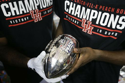 <div class='meta'><div class='origin-logo' data-origin='none'></div><span class='caption-text' data-credit='AP Photo/ David Goldman'>Houston players hold the Peach Bowl Troph after the Peach Bowl</span></div>