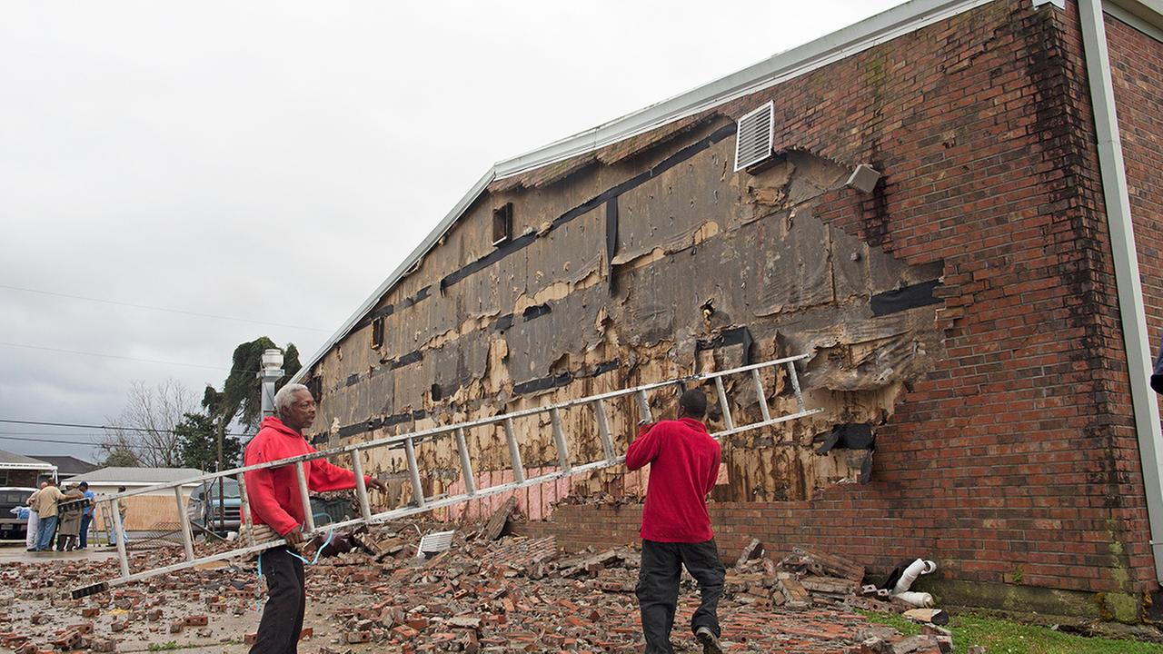 Volunteers Percy Mitchell, left, and Eugene Trice, carry a ladder as they attempt to knock down bricks from the wall of New Mount Bethel Baptist Church, which was damaged by storms