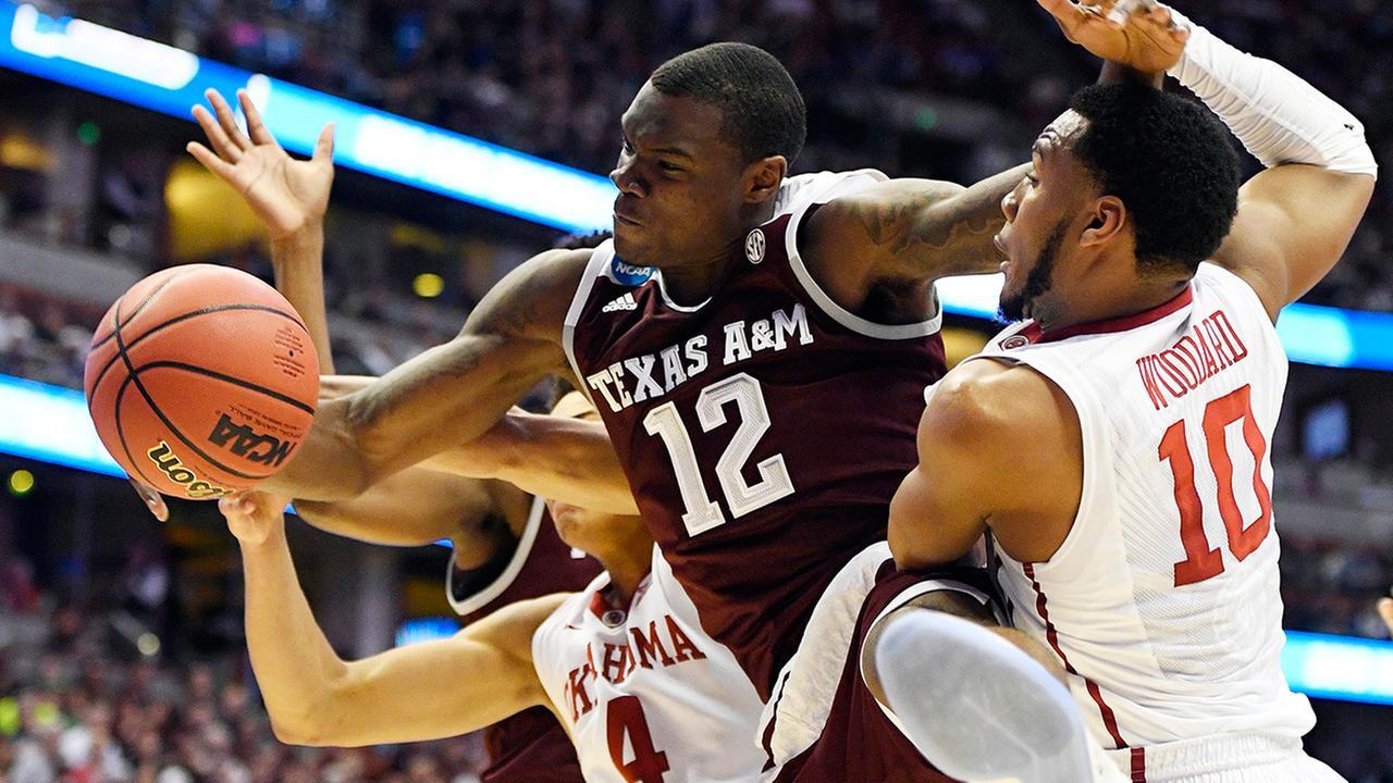 Texas A&M guard Jalen Jones, middle, battles Oklahoma center Jamuni McNeace, left, and guard Jordan Woodard for a rebound during the first half of an NCAA college basketball game.