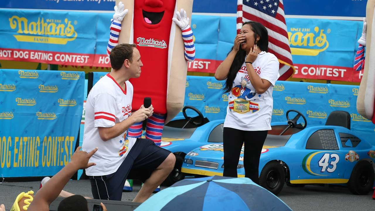 Eating champion Joey Chestnut got on one knee to propose to his girlfriend, Neslie Ricasa, during the annual hot dog eating contest in New York Friday. (AP)
