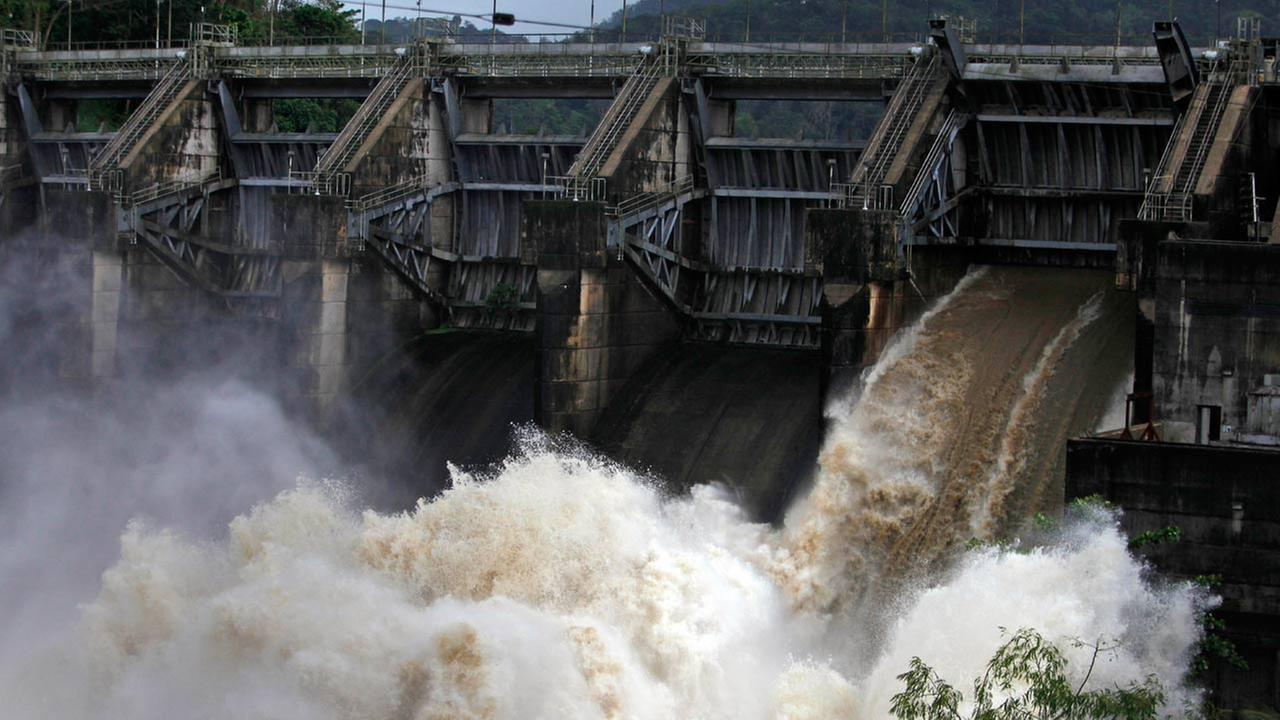 Water rushes through an open bay at the Carraizo Dam to release water left by a passing storm in Trujillo Alto, Puerto Rico, Saturday, Aug. 23, 2014