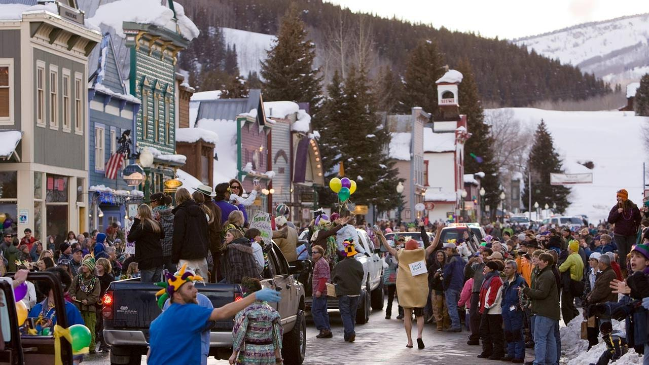 A crowd gathers on Elk Avenue in Crested Butte, Colo., during a Mardi Gras parade celebration