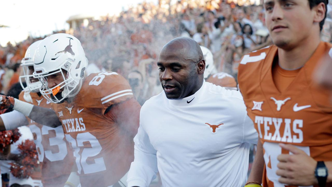 Texas coach Charlie Strong, center, runs on to the field with his team for this first game a