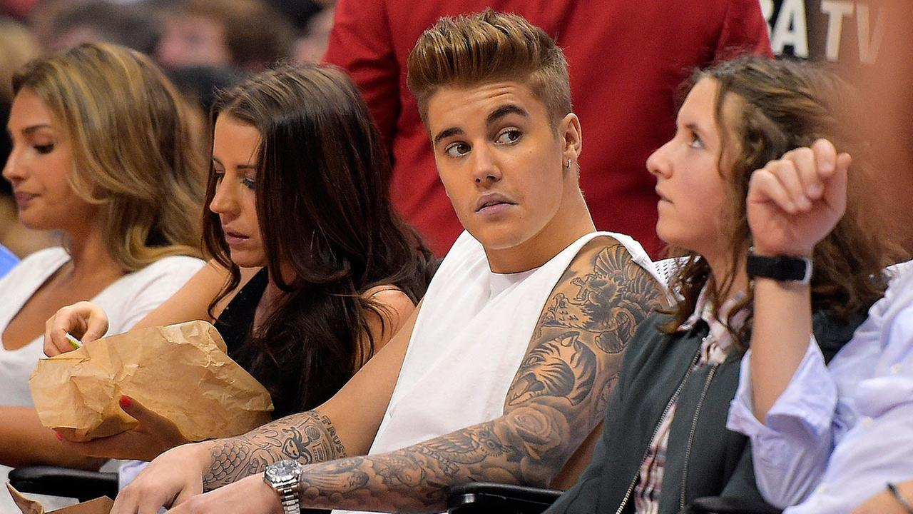This May 11, 2014 photo shows singer Justin Bieber, center, watching the Los Angeles Clippers play the Oklahoma City Thunder with his mother Pattie Mallette, second from left.