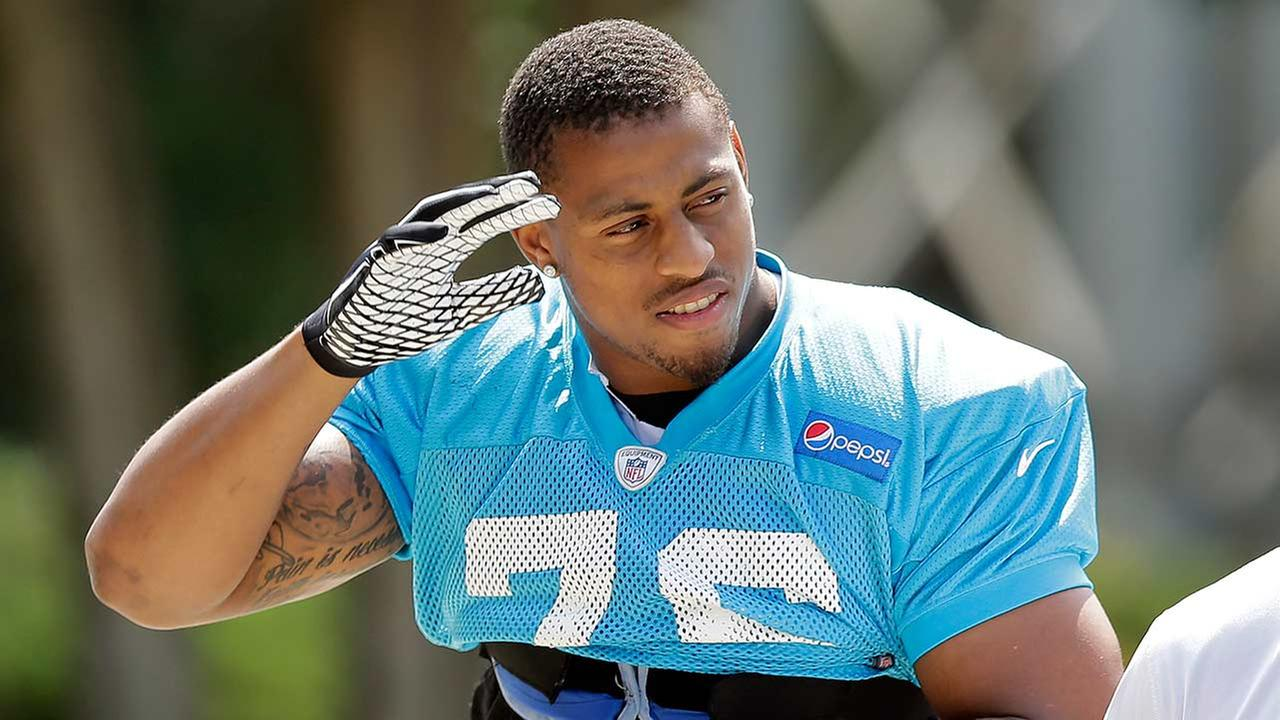 Carolina Panthers Greg Hardy waves to fans as he arrives for an NFL football practice in Charlotte, N.C., Thursday, Sept. 11, 2014