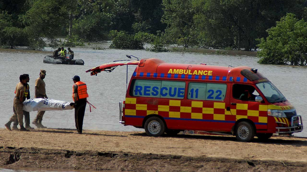 Pakistan army soldiers and a rescue worker carry the body of a person into an ambulance after recovering from floodwaters in a village near Multan, Pakistan