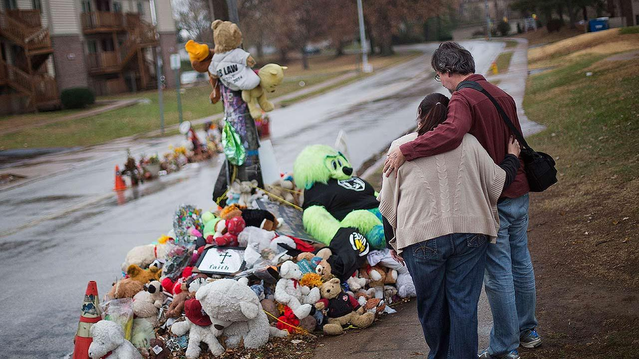 A couple embraces while looking over the sidewalk memorial near the spot where Michael Brown was shot and killed in Ferguson, Missouri.