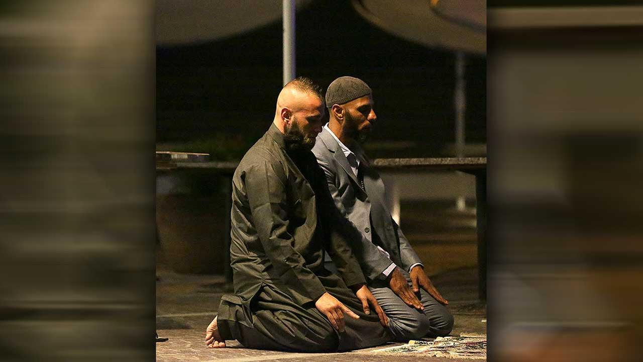 Sam Tiger right, and Abdulrahman El-Lawn perform prayers after a cafe siege in the central business district of Sydney, Australia, Tuesday, Dec. 16, 2014