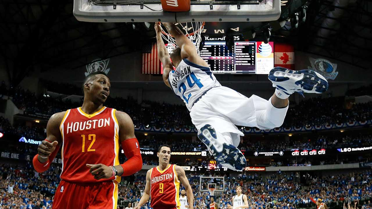Houston Rockets Dwight Howard (12) and Pablo Prigioni (9) of Argentina watch as Dallas Mavericks Richard Jefferson (24) holds on to the rim on a dunk
