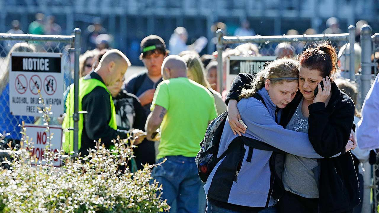 Parents and students walk away from an area at North Thurston High School Monday, April 27, 2015, where students were released to their parents after a shooting at the school