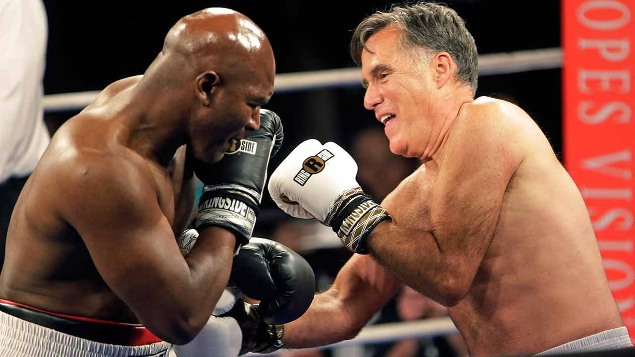 Former Republican presidential candidate Mitt Romney, right, throws punches with five-time heavyweight boxing champion Evander Holyfield at a charity fight