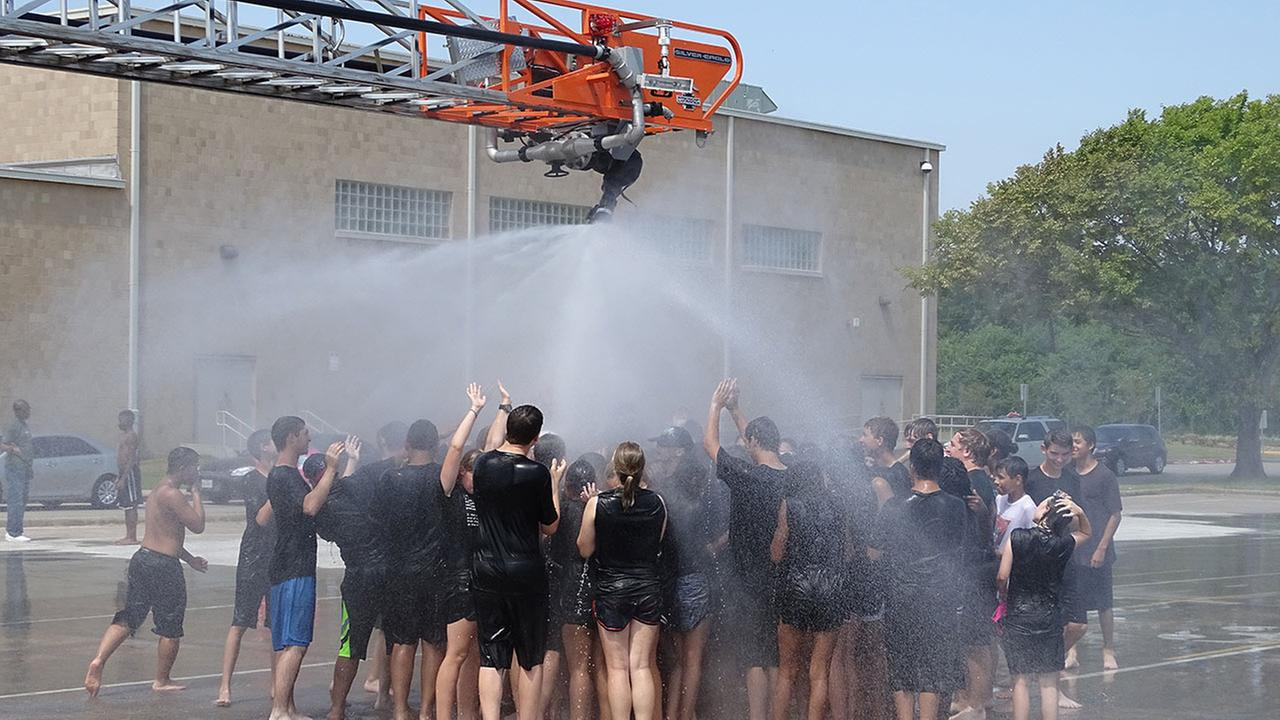 Firefighters from the Forest Bend Fire Department help the Clear Brook High School band students beat the heat