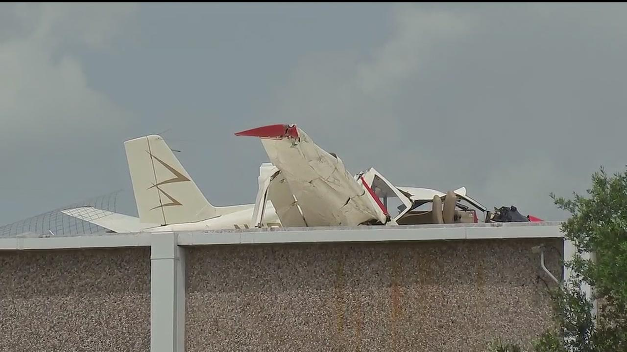 Small plane crash lands on building roof