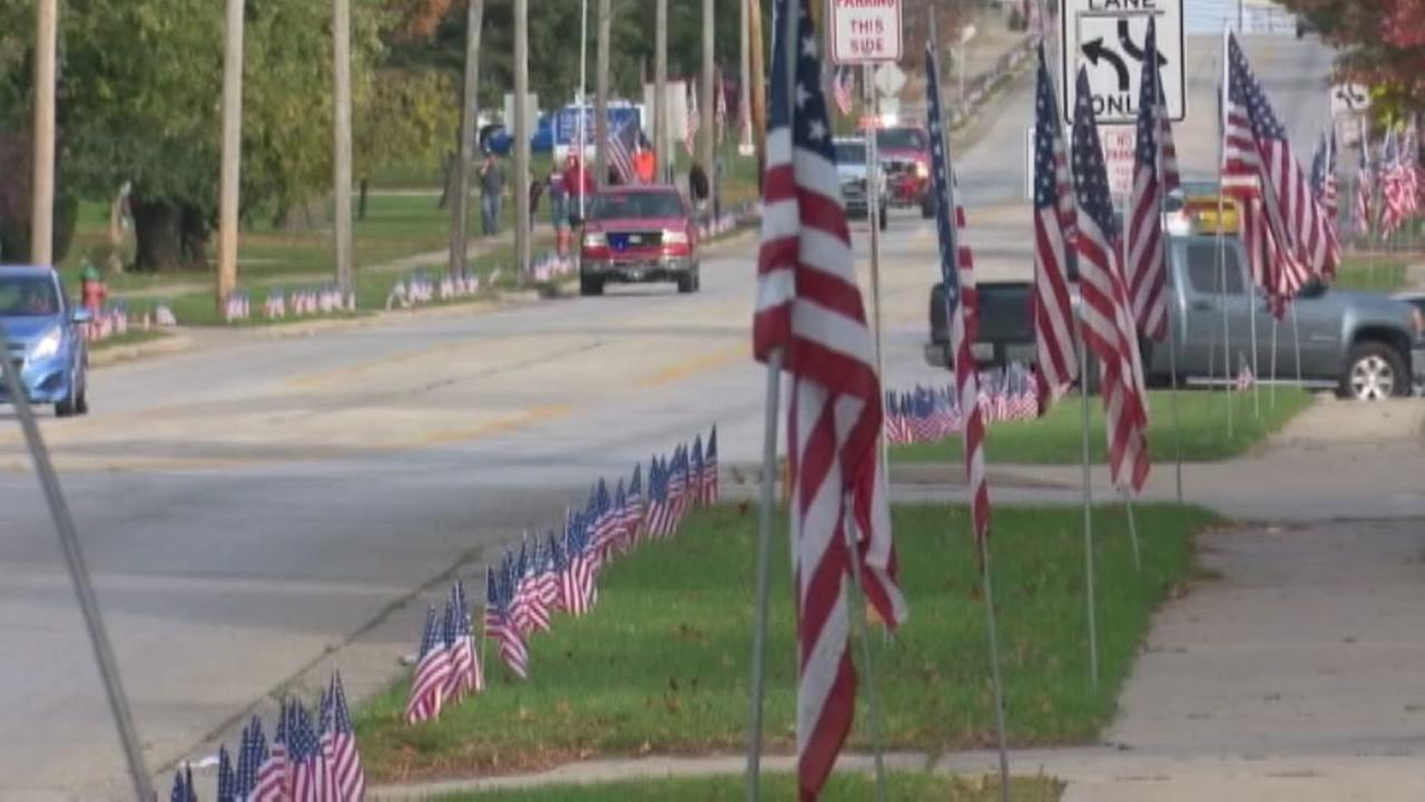 Mourners line fallen soldiers procession with thousands of flags