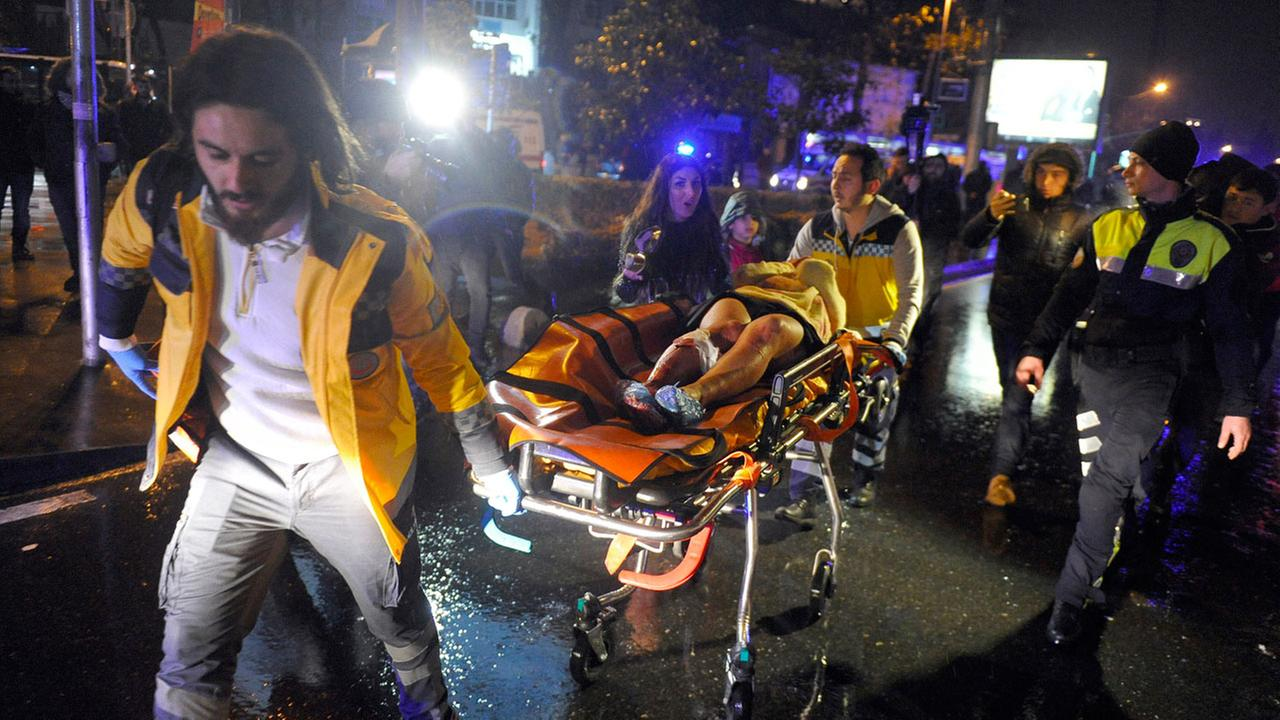 Medics carry a wounded person at the scene after an attack at a popular nightclub in Istanbul, early Sunday, Jan. 1, 2017.IHA via AP