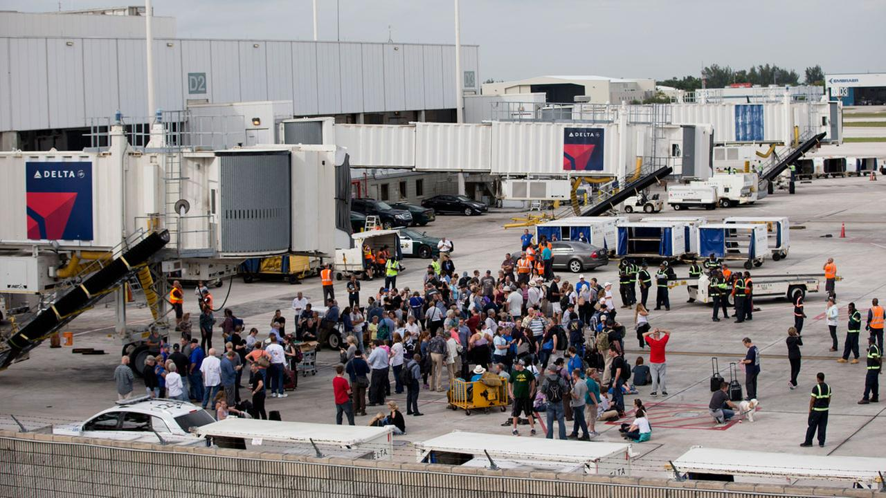 People stand on the tarmac at the Fort Lauderdale-Hollywood International Airport after a shooter opened fire inside a terminal of the airport, killing several people.