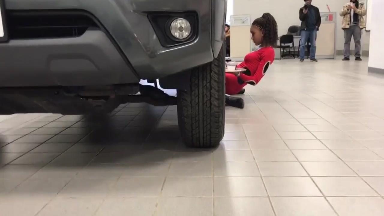 Woman limbos under SUV