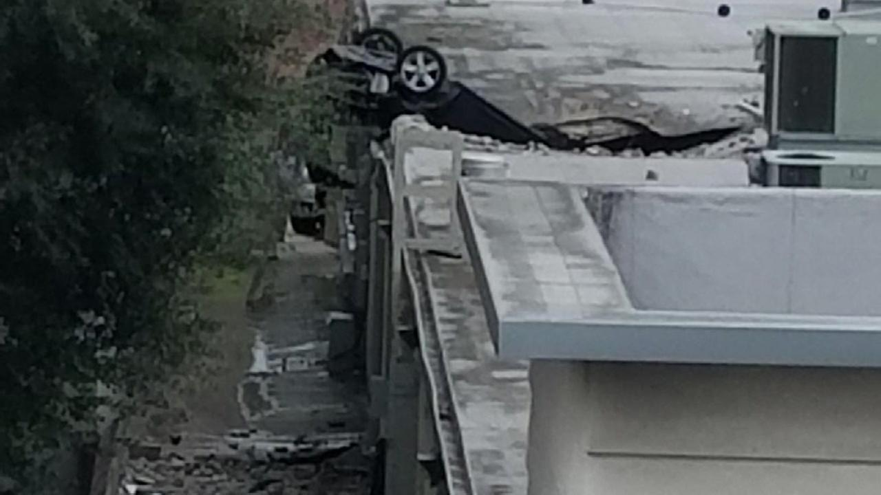Car drives off parking garage deck to building below