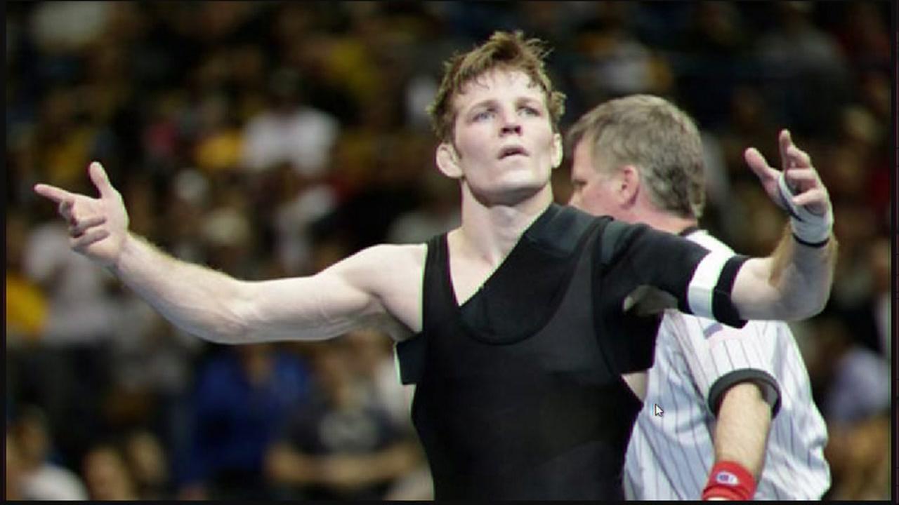 WATCH: Iowa wrestler wins national title, tosses assistant coach