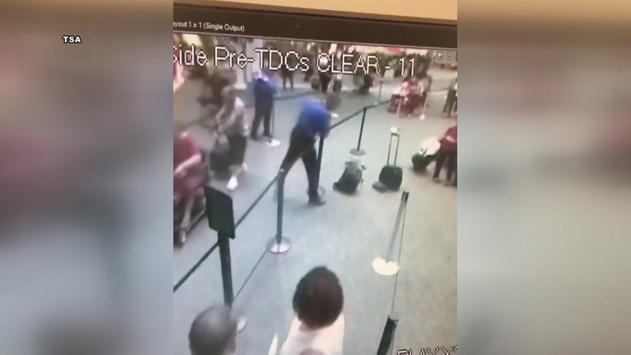 TSA agent acts quickly when backpack smokes in security line