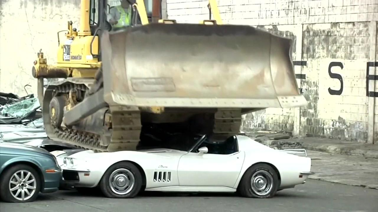 Bulldozer crushes 20 luxury cars