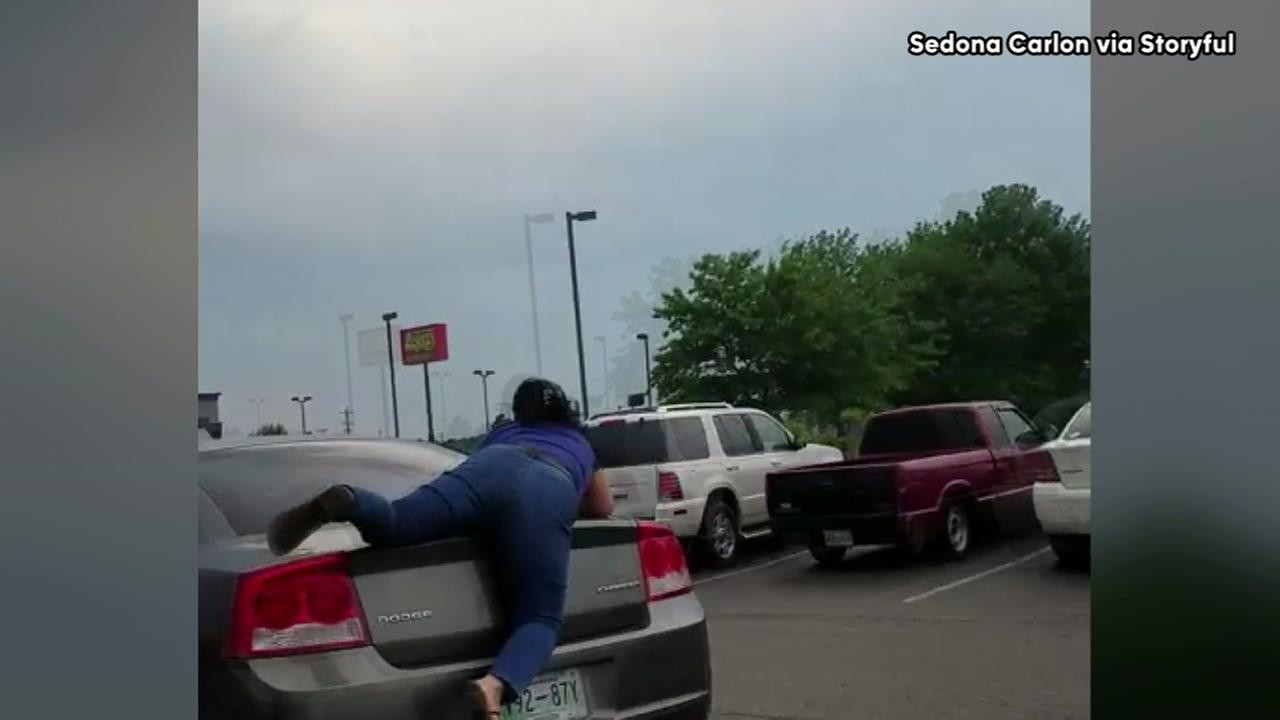 Woman clings to moving car during parking lot argument