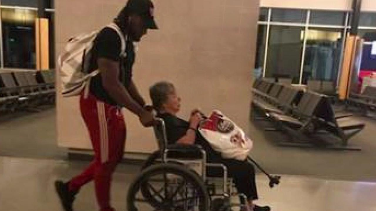 Aaron Jones helps woman in wheelchair at airport