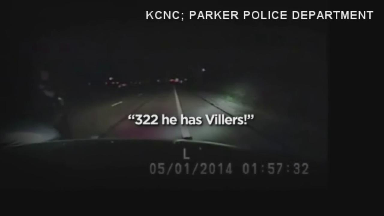 Officer clings to car during chase