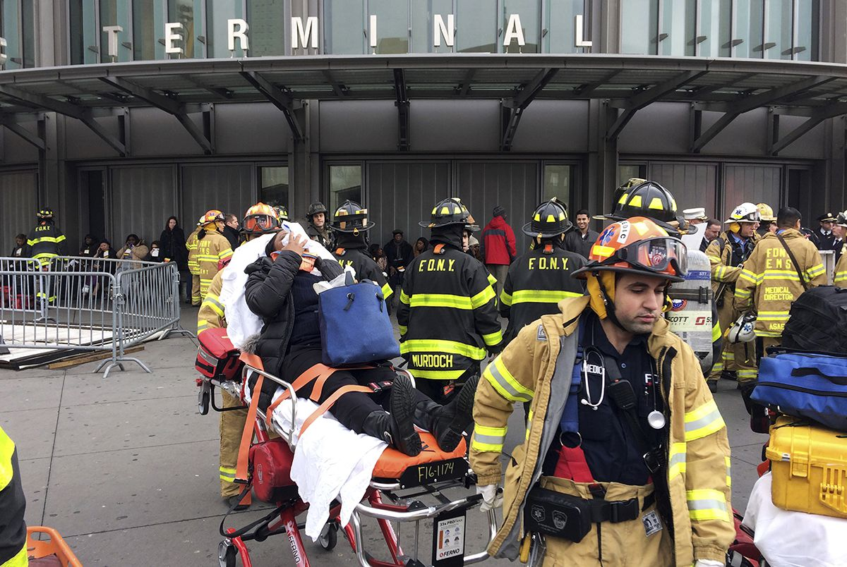 <div class='meta'><div class='origin-logo' data-origin='AP'></div><span class='caption-text' data-credit='AP Photo/Mark Lennihan'>An injured passenger, after a Long Island Rail Road commuter train either hit something or derailed, is taken from the Atlantic Terminal, in the Brooklyn borough of New York.</span></div>