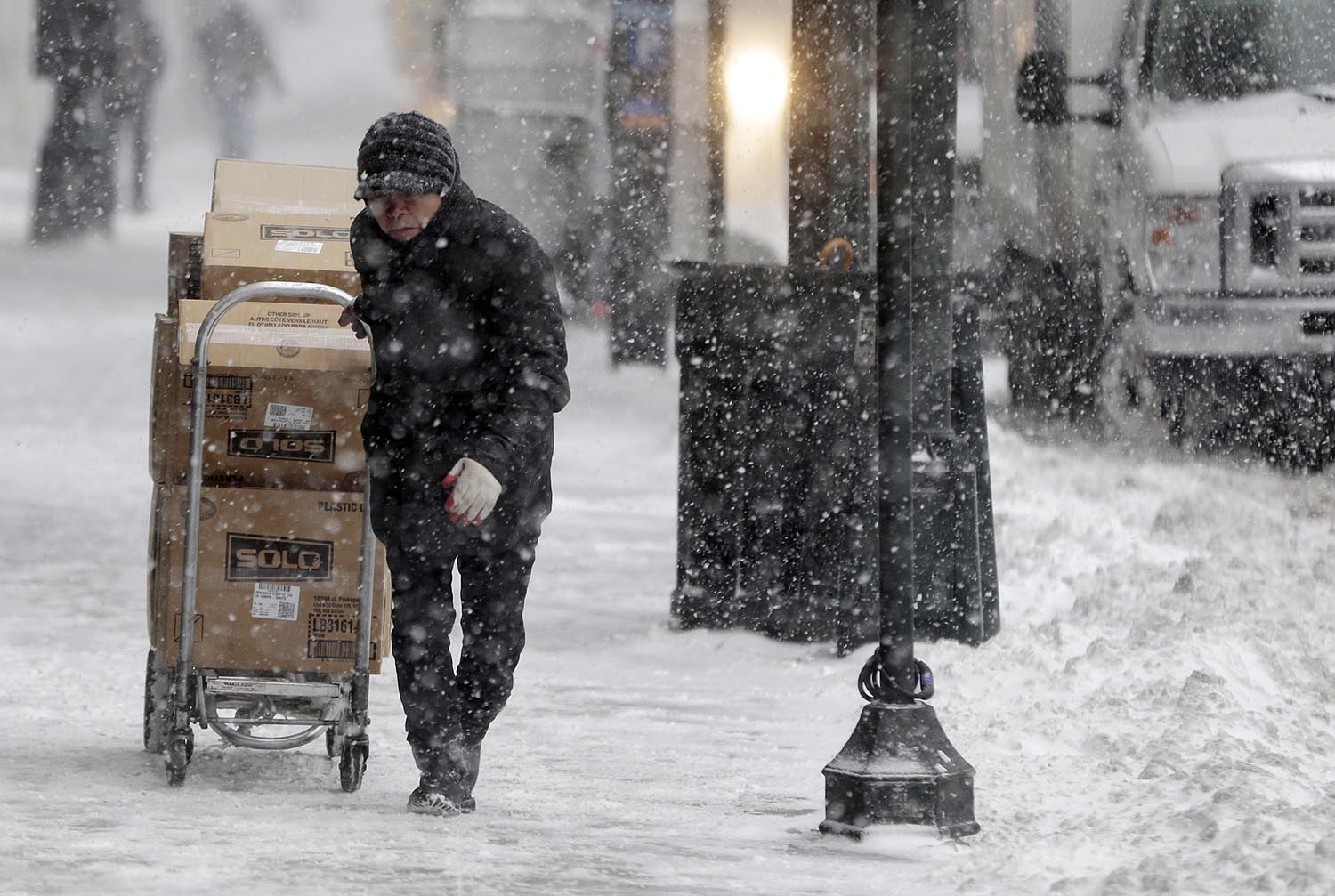 <div class='meta'><div class='origin-logo' data-origin='AP'></div><span class='caption-text' data-credit='AP Photo/Seth Wenig'>A man struggles to make a delivery through snowy streets in New York, Thursday, Jan. 4, 2018.</span></div>