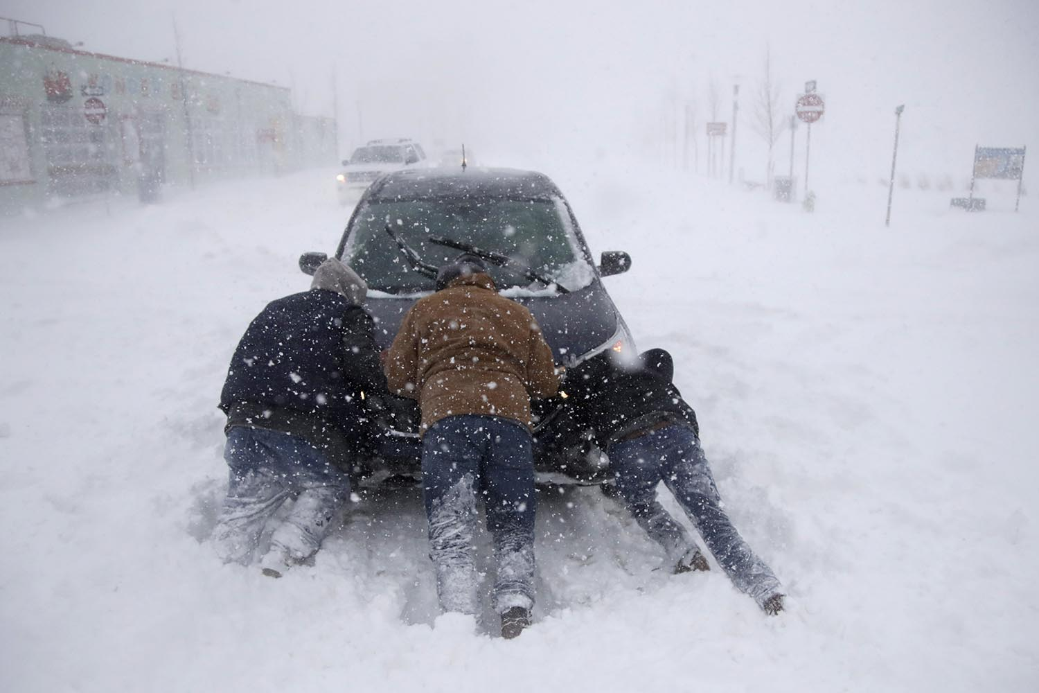 <div class='meta'><div class='origin-logo' data-origin='AP'></div><span class='caption-text' data-credit='AP Photo/Julio Cortez'>A group of men help a motorist after his vehicle was stuck in the snow near Asbury Park boardwalk during a snowstorm, Thursday, Jan. 4, 2018, in Asbury Park, N.J.</span></div>