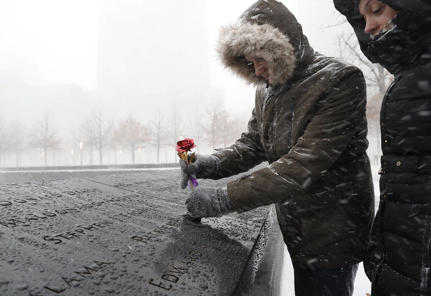 <div class='meta'><div class='origin-logo' data-origin='AP'></div><span class='caption-text' data-credit='AP Photo/Kathy Willens'>Tara Chandler, right, watches her husband Joshua place a metal rose on the border of one of the fountains at the National September 11 Memorial and Museum in New York, Jan 4, 2018.</span></div>