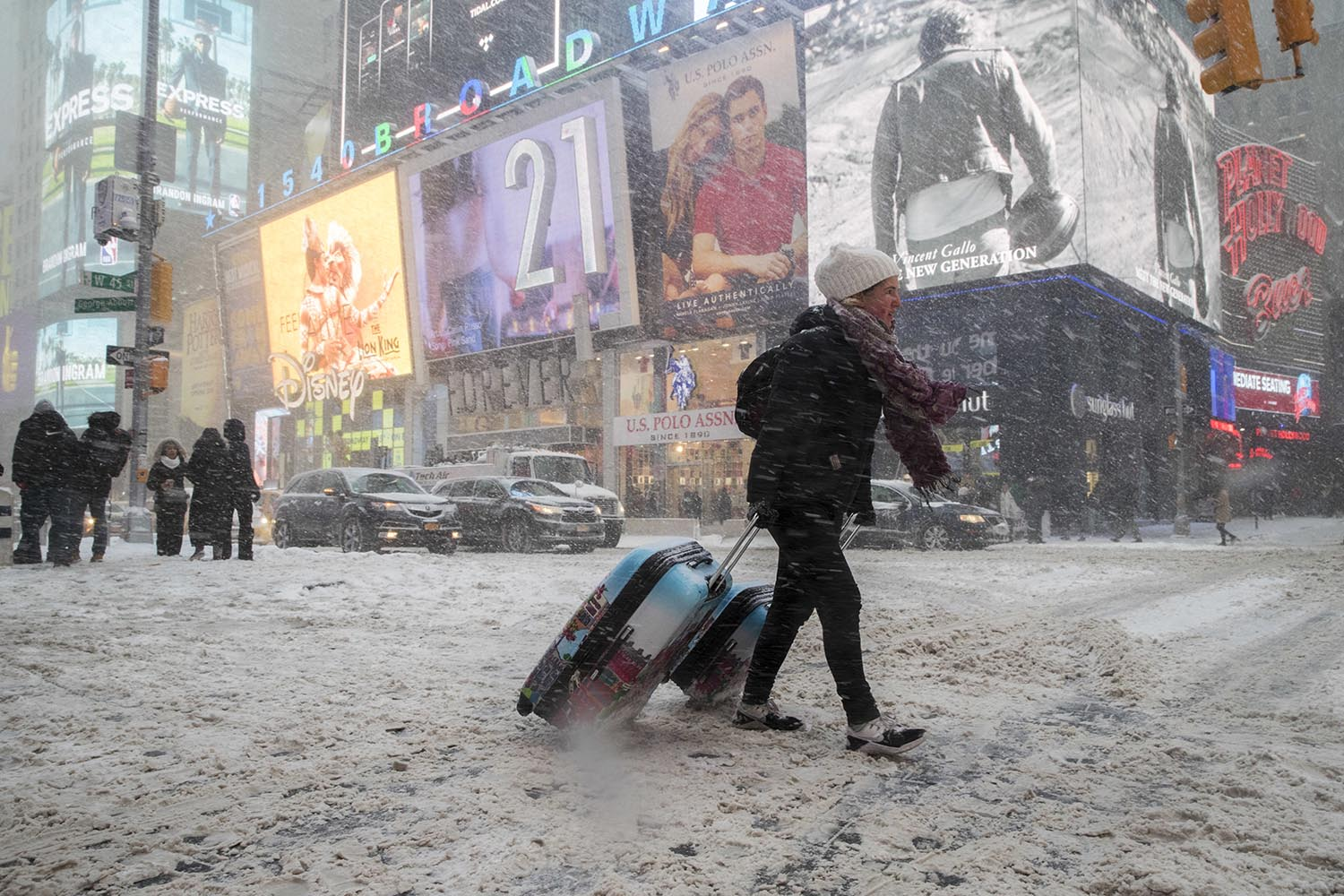 <div class='meta'><div class='origin-logo' data-origin='AP'></div><span class='caption-text' data-credit='AP Photo/Mary Altaffer'>Rebecca Hollis of New Zealand drags her suitcases in a snowstorm through Times Square on her way to a hotel, Thursday, Jan. 4, 2018, in New York.</span></div>