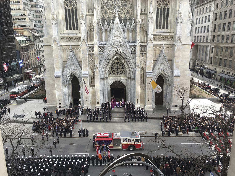 <div class='meta'><div class='origin-logo' data-origin='AP'></div><span class='caption-text' data-credit='Richard Drew'>A firetruck arrives at New York's St. Patrick's Cathedral bearing the body of Lt. Michael Davidson as mourners gathered.</span></div>