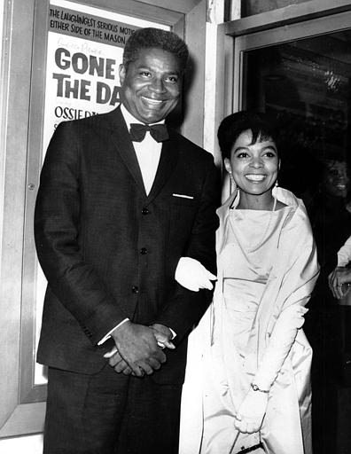 Ossie Davis, left, and Ruby Dee pose in front of their movie poster at the opening night gala of their film
