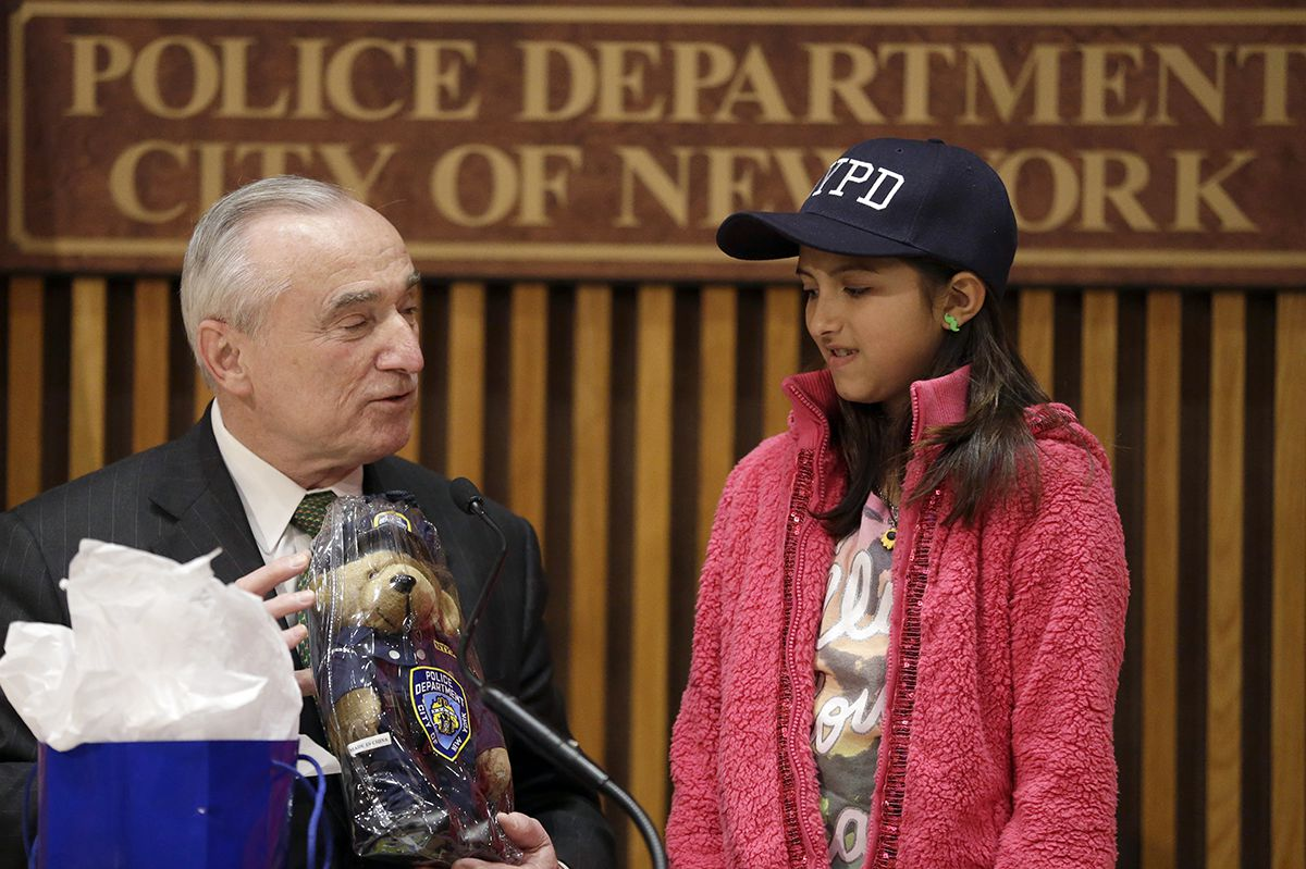 <div class='meta'><div class='origin-logo' data-origin='AP'></div><span class='caption-text' data-credit='AP Photo/Mary Altaffer'>NYPD Commissioner Bill Bratton, left, presents Savannah Solis, of Tyler, Texas, a gift during a news conference at New York City police headquarters, Wednesday, Feb. 25, 2015.</span></div>