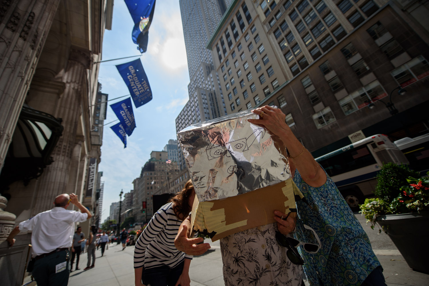 <div class='meta'><div class='origin-logo' data-origin='WABC'></div><span class='caption-text' data-credit='WABC Photo/Mike Waterhouse'>People in Midtown Manhattan paused for a moment and used a pinhole device to watch the solar eclipse on Monday, Aug. 21, 2017.</span></div>