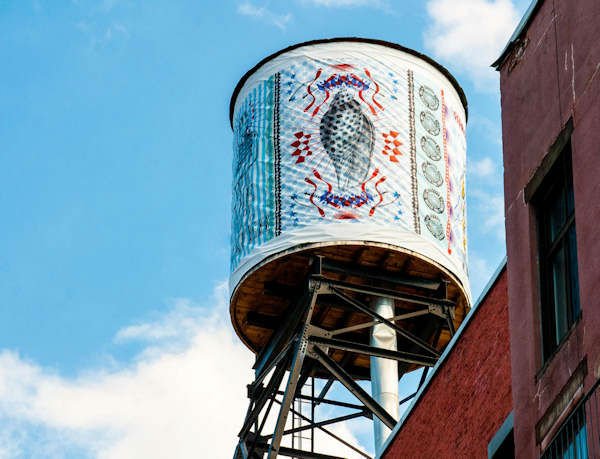 """<div class=""""meta image-caption""""><div class=""""origin-logo origin-image """"><span></span></div><span class=""""caption-text"""">Artwork by acclaimed artists and New York City public school students is wrapped around rooftop water tanks throughout New York City. (Photo/The Water Tank Project)</span></div>"""