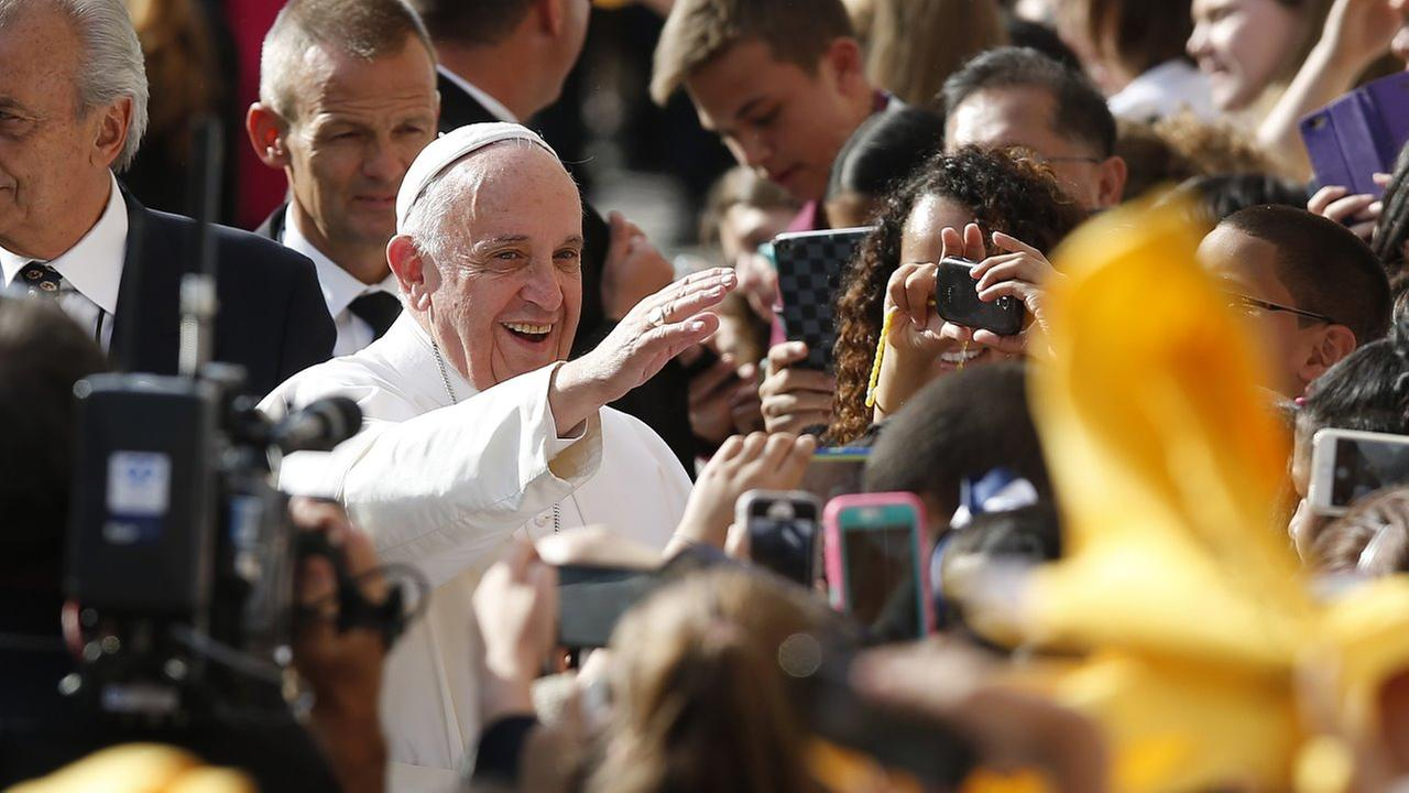 Pope Francis greets the faithful as he arrives at Our Lady Queen of Angels School, Friday, Sept. 25, 2015, in New York.