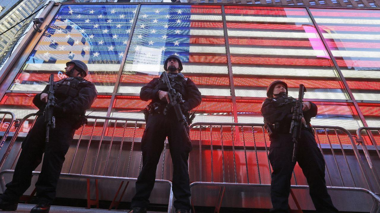 Heavily armed New York city police officers with the Strategic Response Group stand guard at the armed forces recruiting center in New Yorks Times Square, Saturday, Nov. 14, 2015.