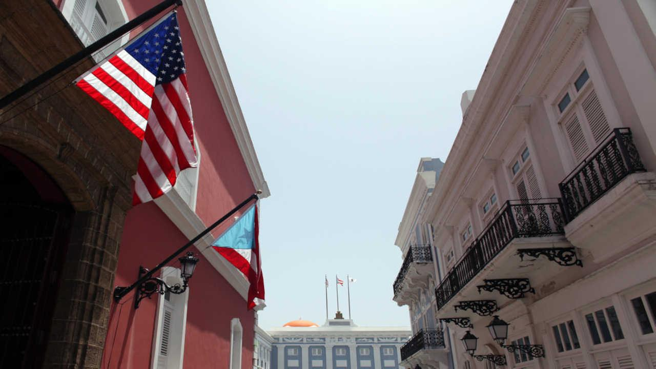 The U.S. and Puerto Rico flags wave in front of the governors mansion in Old San Juan, Puerto Rico.