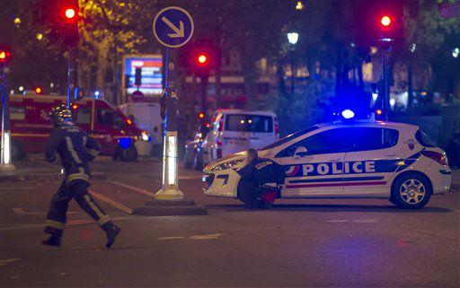 <div class='meta'><div class='origin-logo' data-origin='none'></div><span class='caption-text' data-credit='AP Photo/ Kamil Zihnioglu'>A police officer takes cover behind a car while a rescue worker runs outside the Bataclan theater  in Paris, France, Wednesday, Nov. 13, 2015.</span></div>