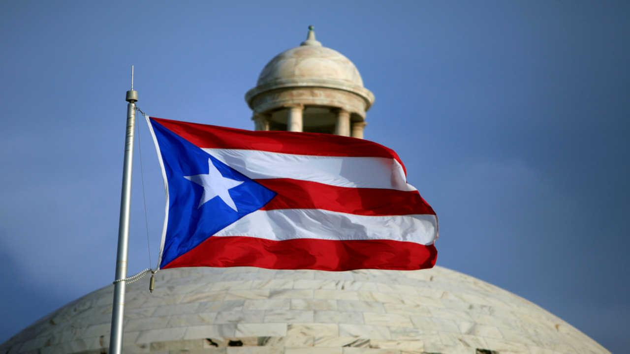 In this Wednesday, July 29, 2015 photo, the Puerto Rican flag flies in front of Puerto Ricos Capitol as in San Juan, Puerto Rico.